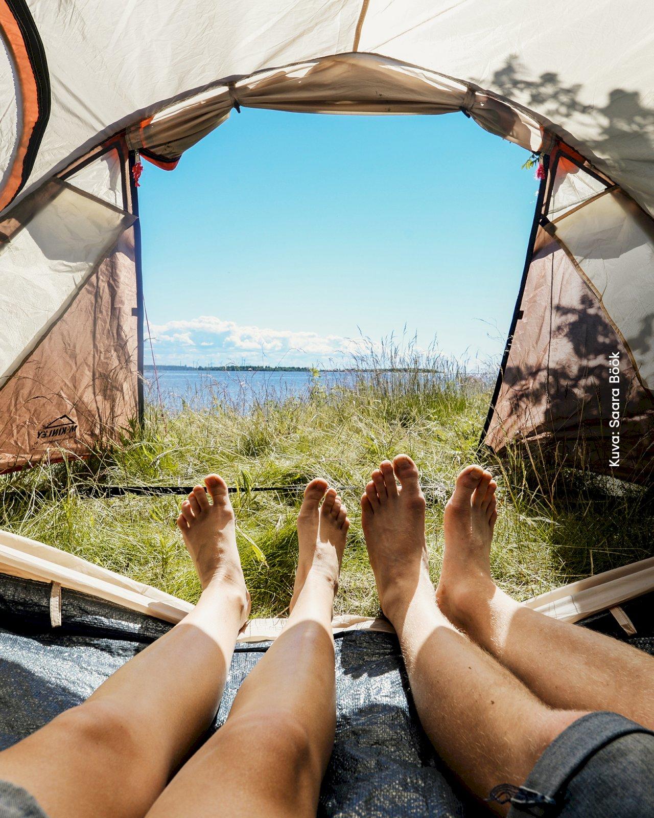 Kaksi retkeilijää makoilevat teltassa katsellen teltasta avautuvaa Raahen saaristoa.