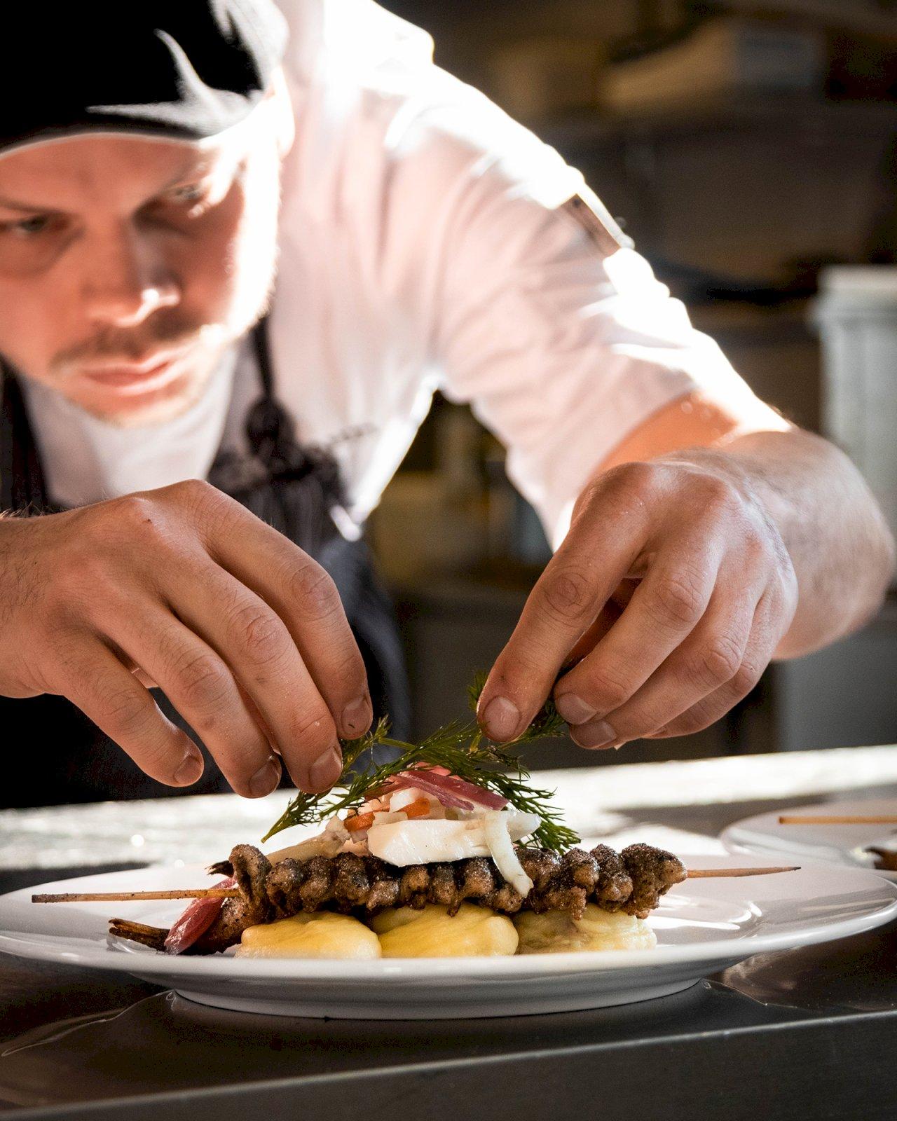 Kokki asettelee käsin ruoka-annoksen päälle tilliä Sahanlahti Resortilla.