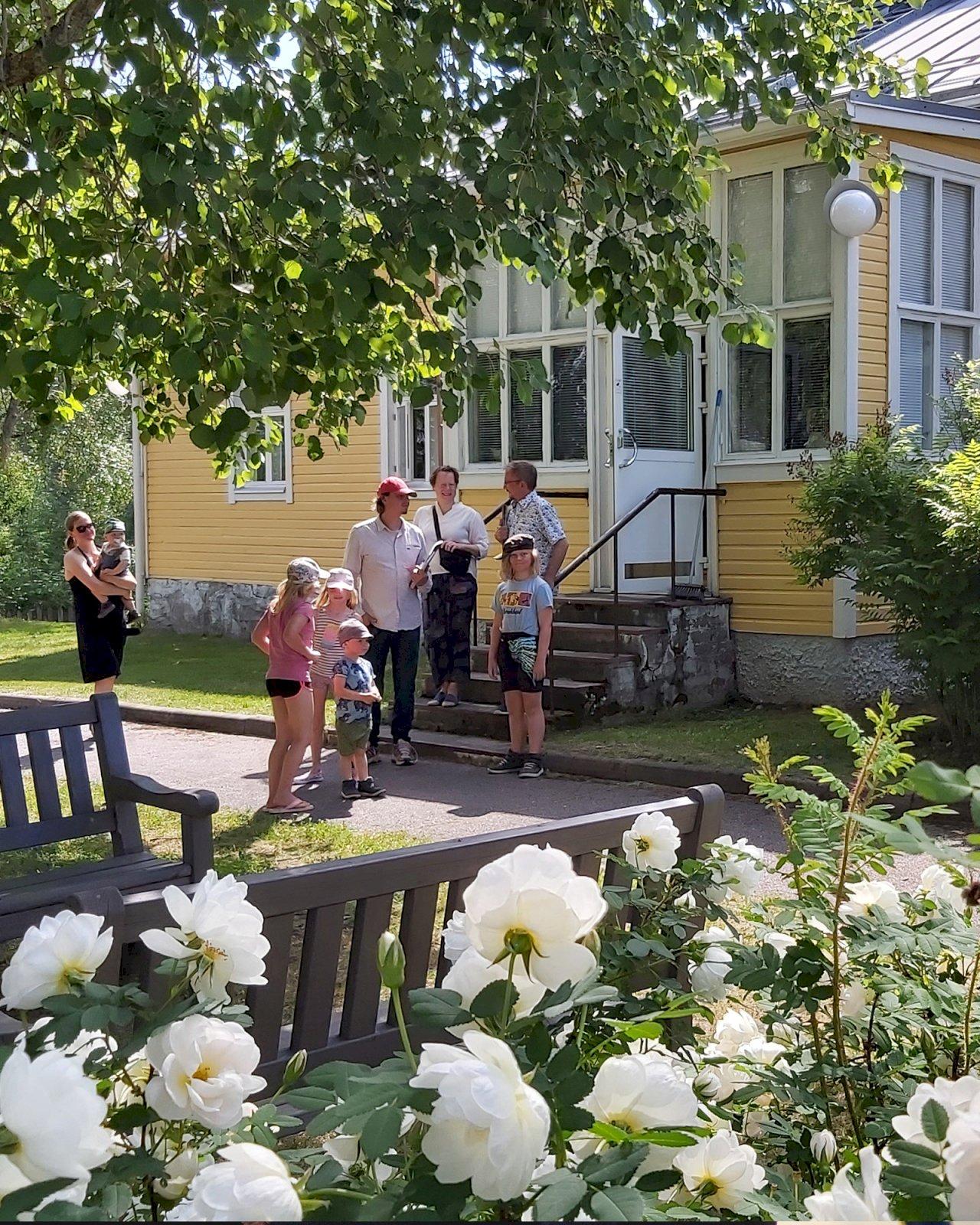 Eino Leino -perinnetalon pihalla Kainuussa seisoo joukko aikuisia ja lapsia.