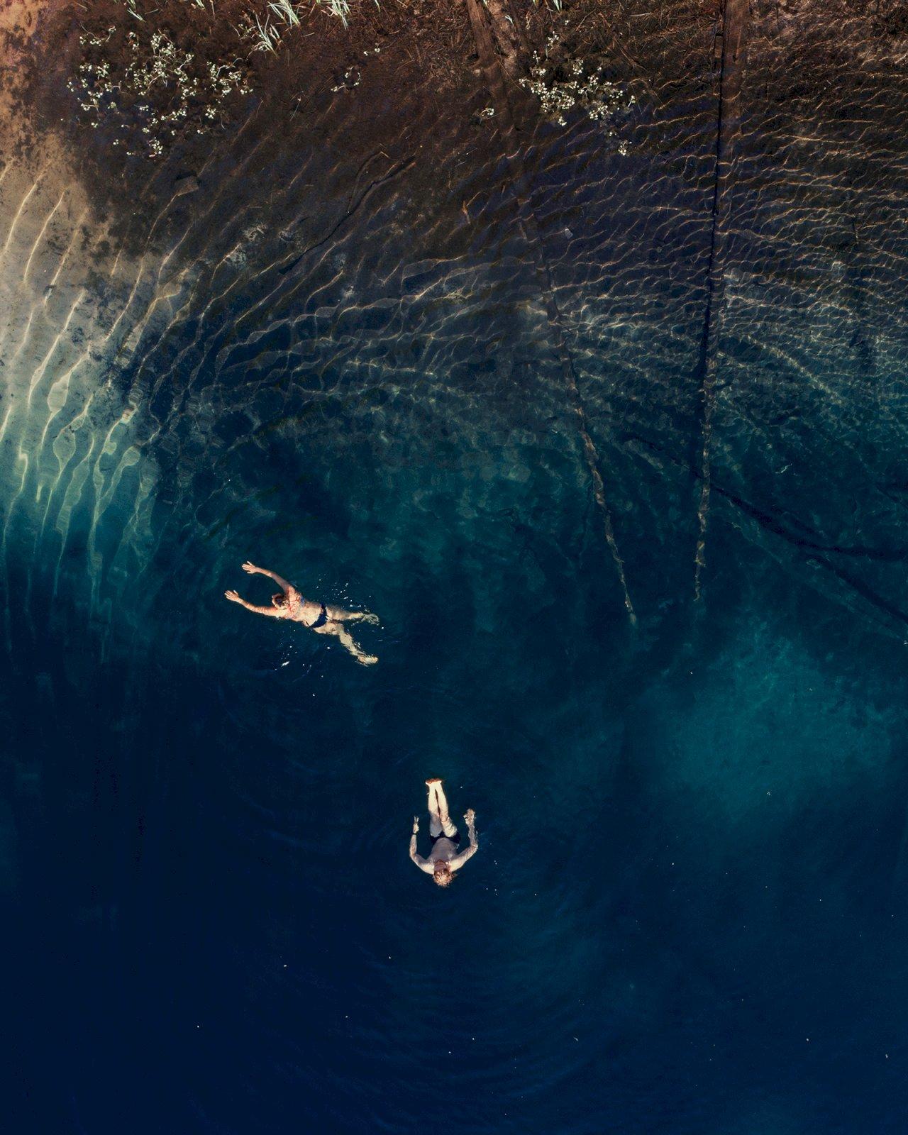 Kaksi henkilöä uivat kirkkaassa suppalammessa Rokuan kansallispuistossa.