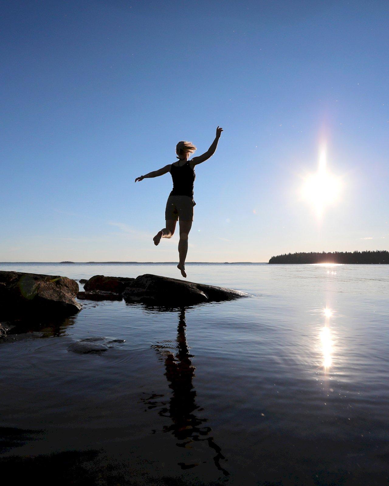 Nainen hyppää ilmaan rantakalliolta Oulujärven rannalla.