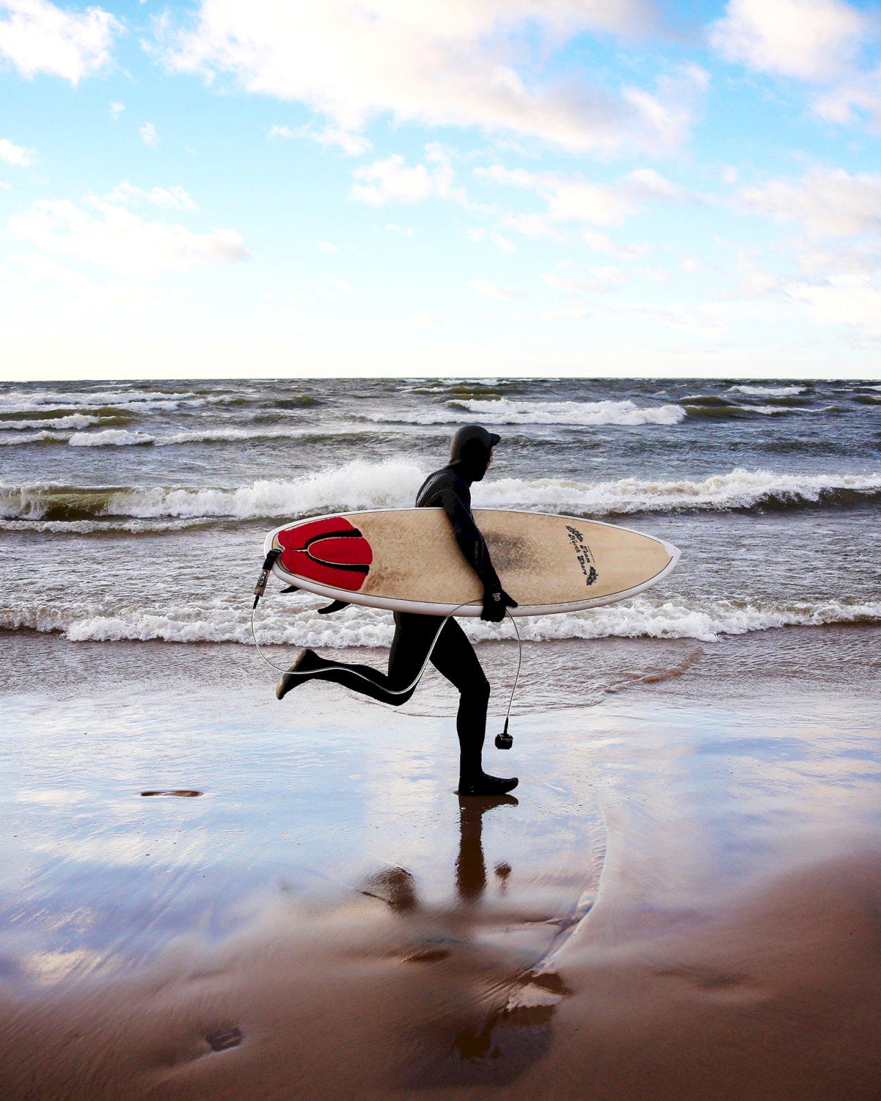 Surffaaja juoksee surffilauta kädessään Oulun rannalla.