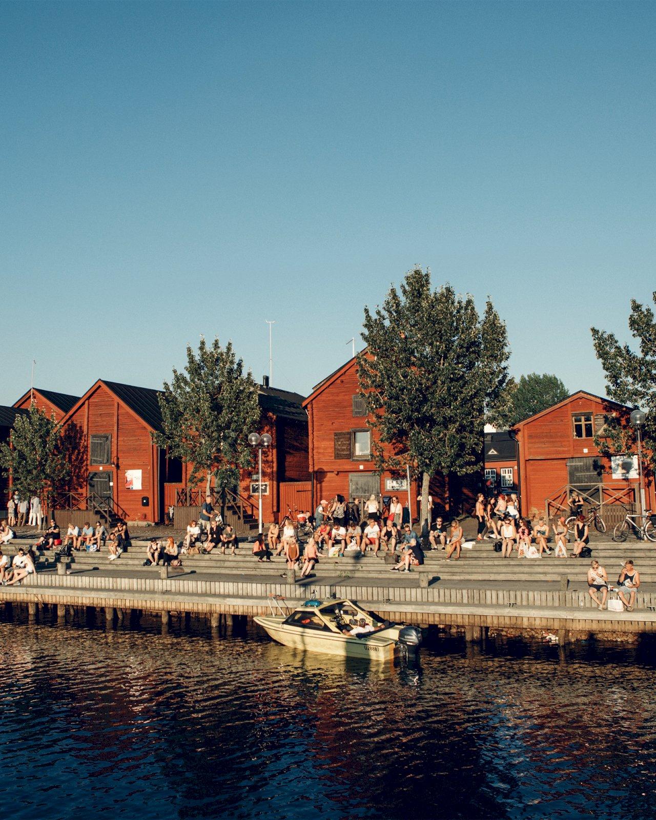 Ihmiset istuvat Oulun Torinrannassa punaisten ranta-aittojen edustalla.