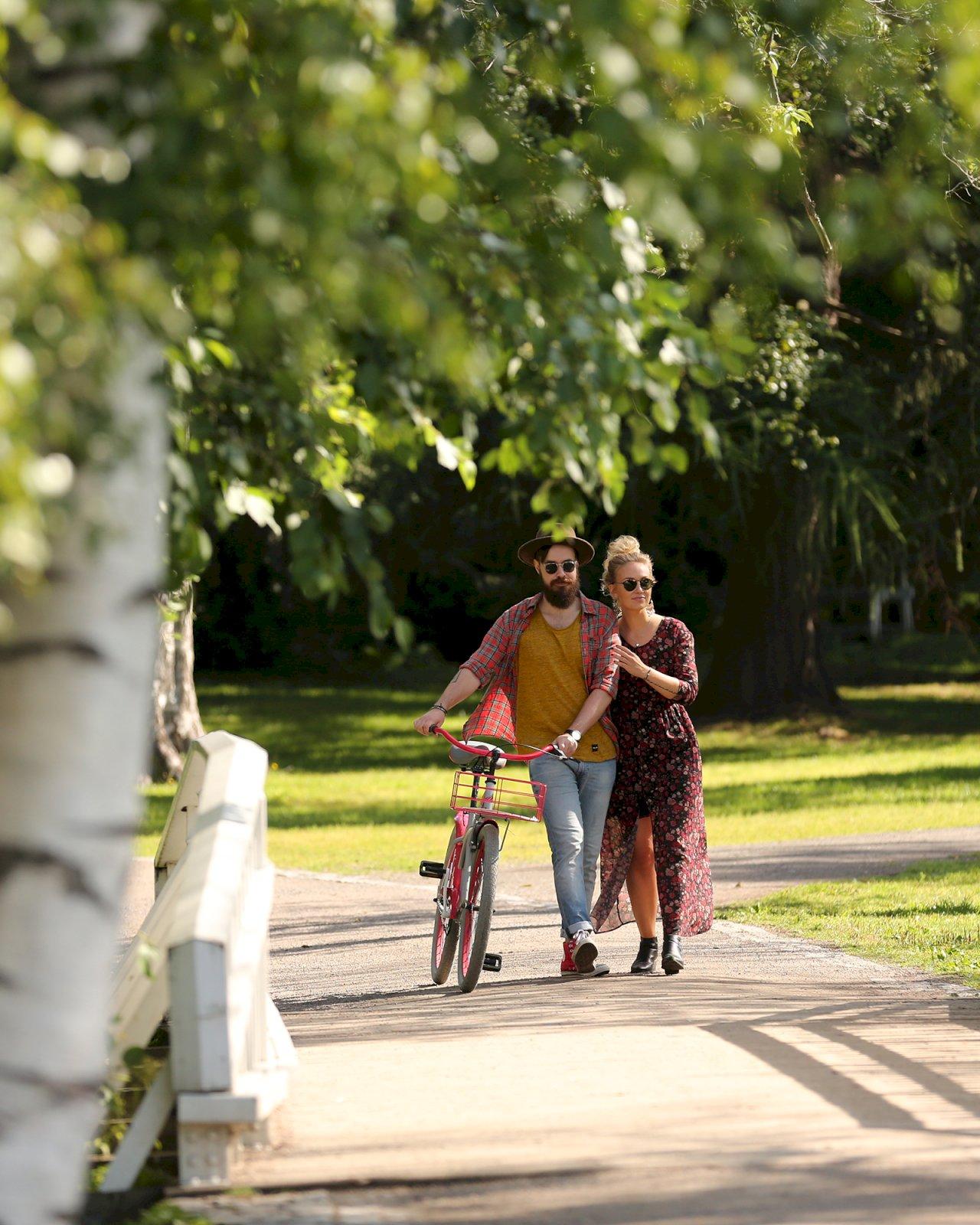 Mies ja nainen kävelevät Oulun puistossa sillan yli taluttaen pyörää.