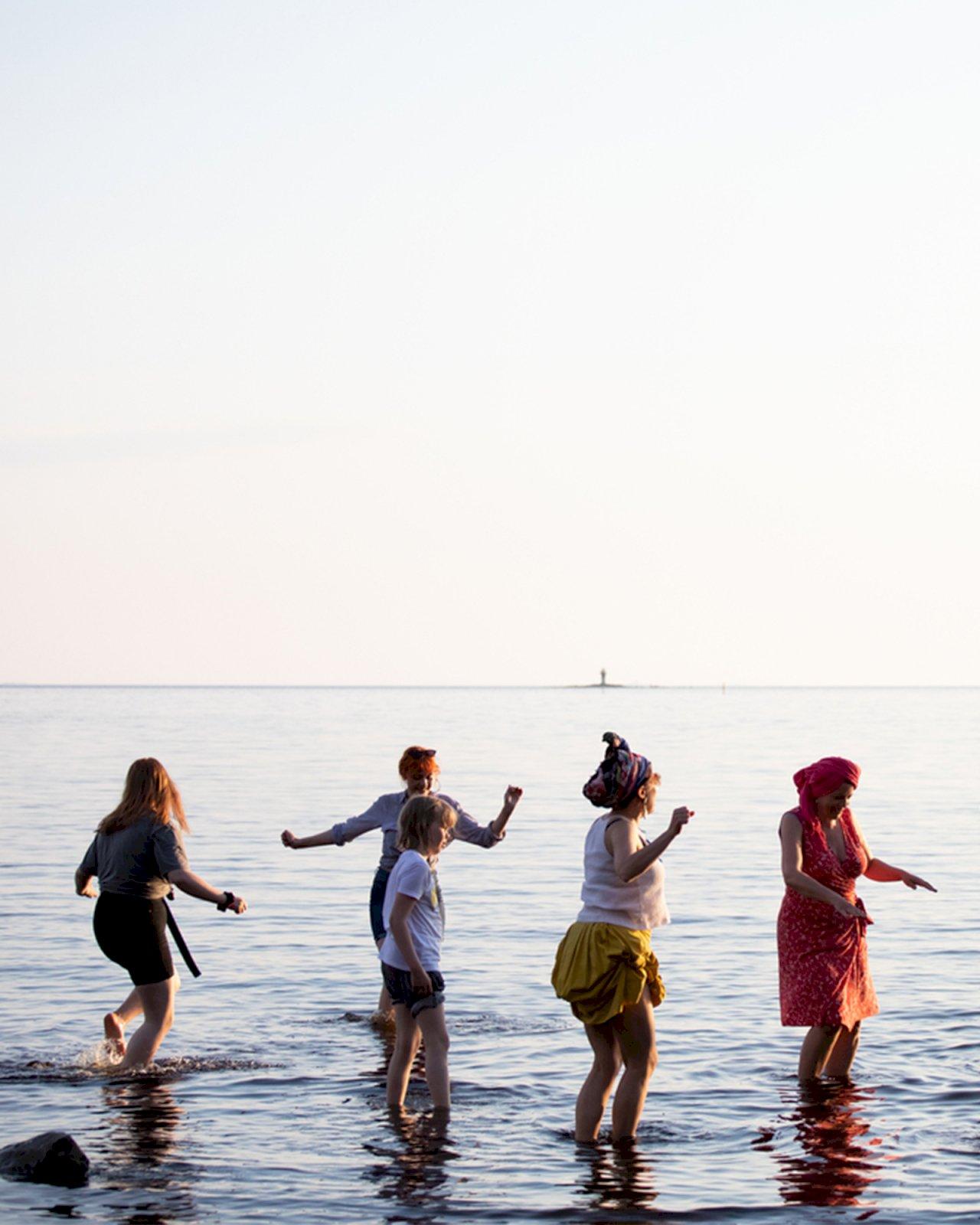 Ihmiset kahlaavat ja tanssivat vedessä festareilla Oulussa.