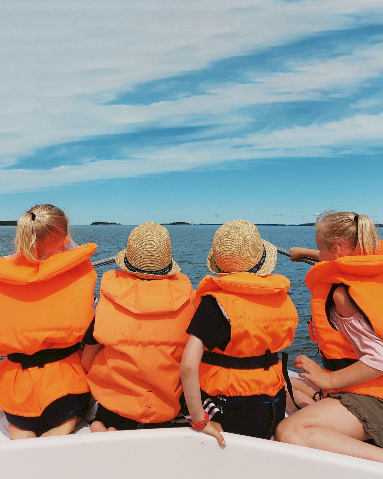 Neljä lasta istuvat veneen keulassa pelastusliivit päällään Porin veneretkellä.