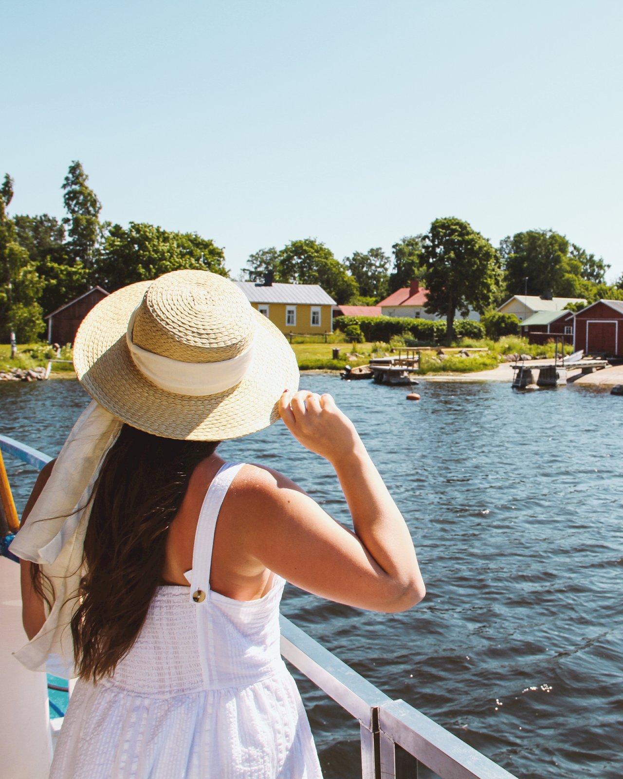 Nainen katselee veneen kannelta kalastajakylän maisemia Kotka-Haminan saaristossa.