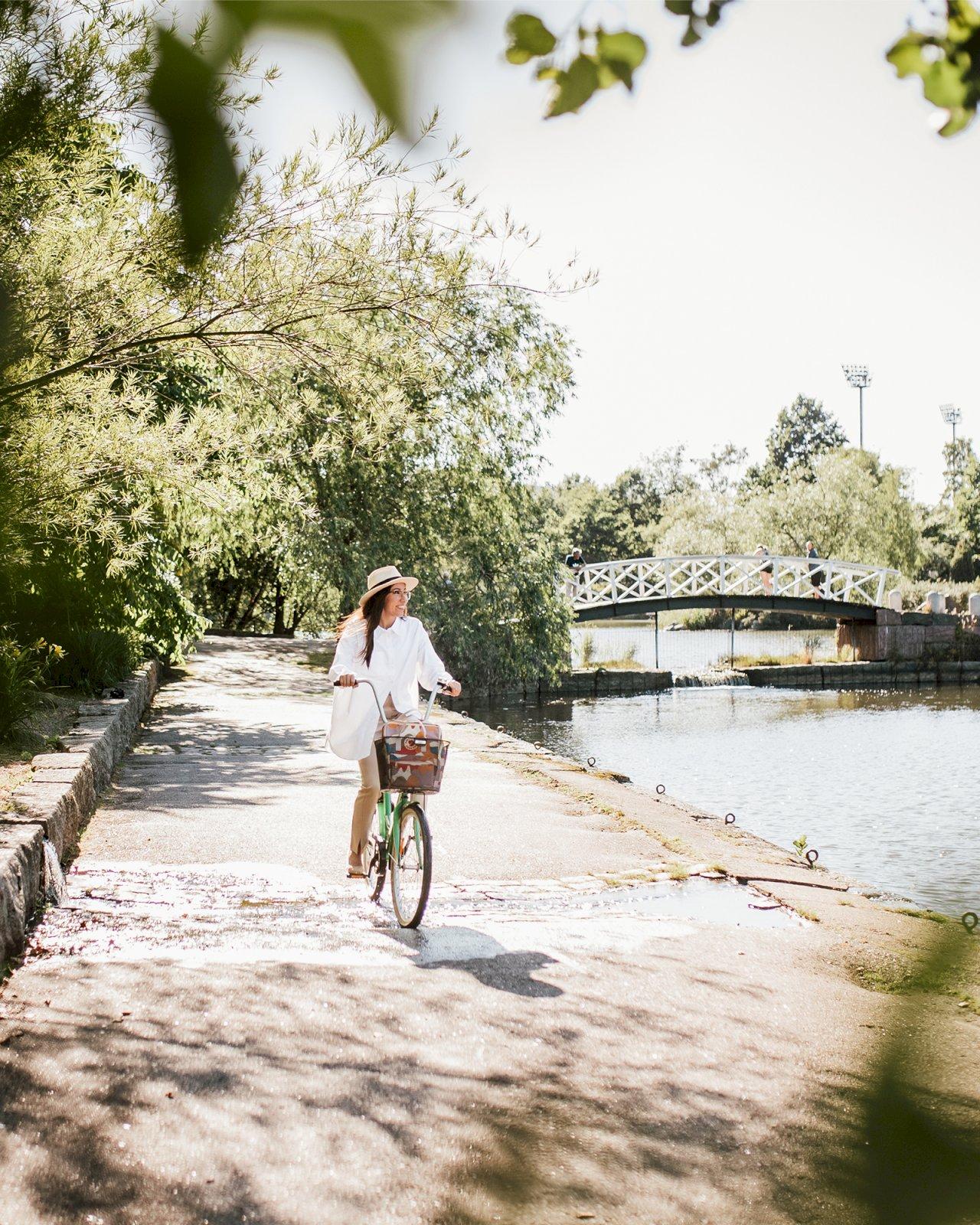 Nainen pyöräilee Sapokan Vesipuistossa Kotkassa.