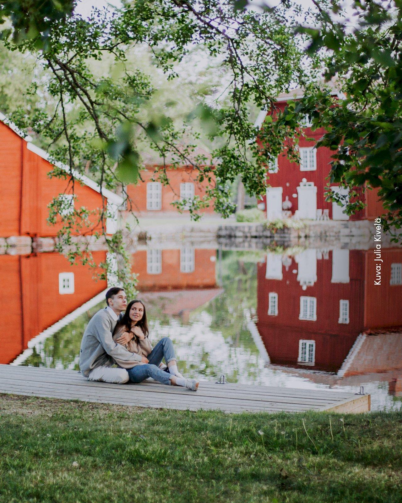 Pariskunta istuu laiturilla Strömforsin ruukkikylässä.