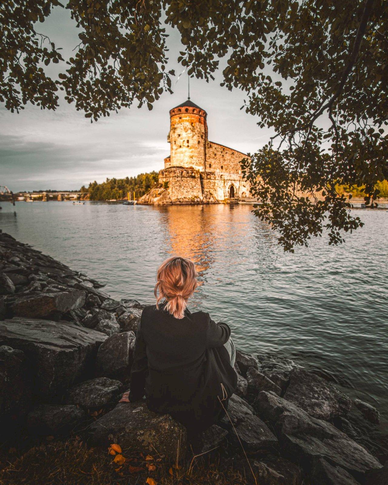Nainen istuu rantakalliolla ja katselee veden ympäröimää Olavinlinnaa.