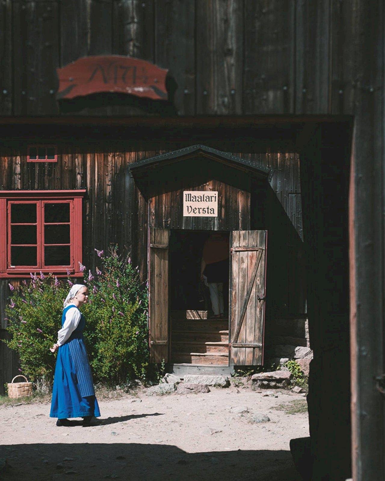 Entisajan käsityöläisen asuun pukeutunut nainen kävelee Turun Luostarinmäellä.