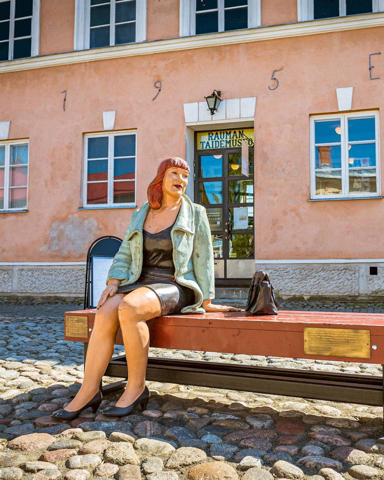 Taiteilija Kerttu Horilan naista esittävä veistos Rauma Flikk istuu penkillä Rauman taidemuseon edessä.