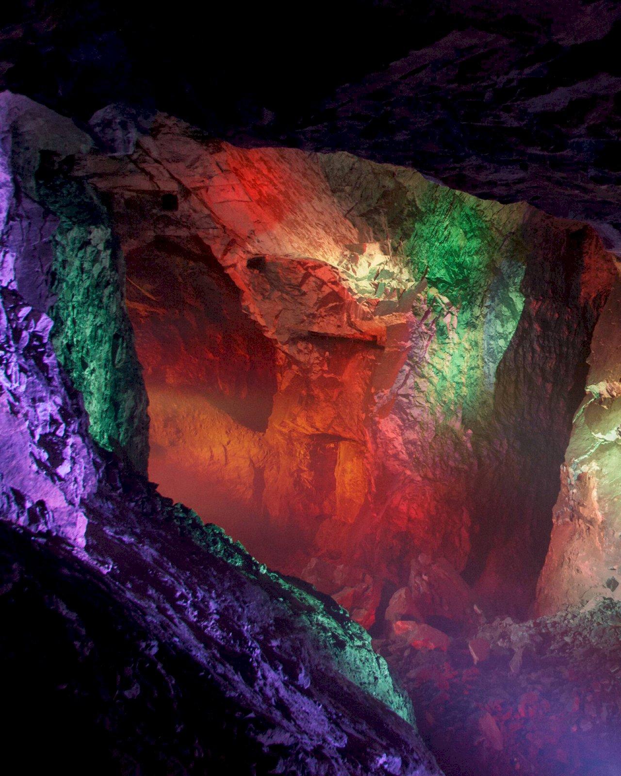 Tytyrin Elämyskaivoksen kallioseinämät on valaistu näyttävästi erivärisillä valoilla.