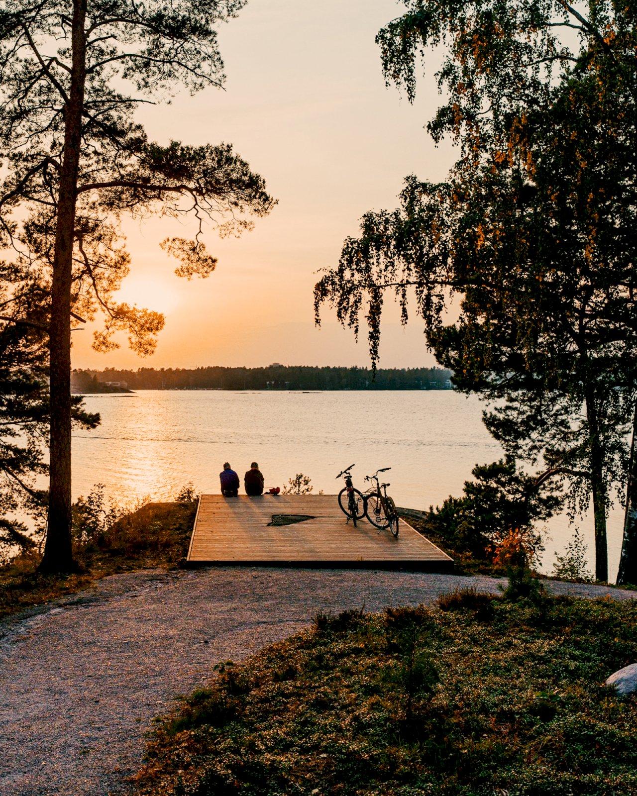 Kaksi ulkoilijaa katselee auringonlaskua Espoon Hanasaaren laiturilla.