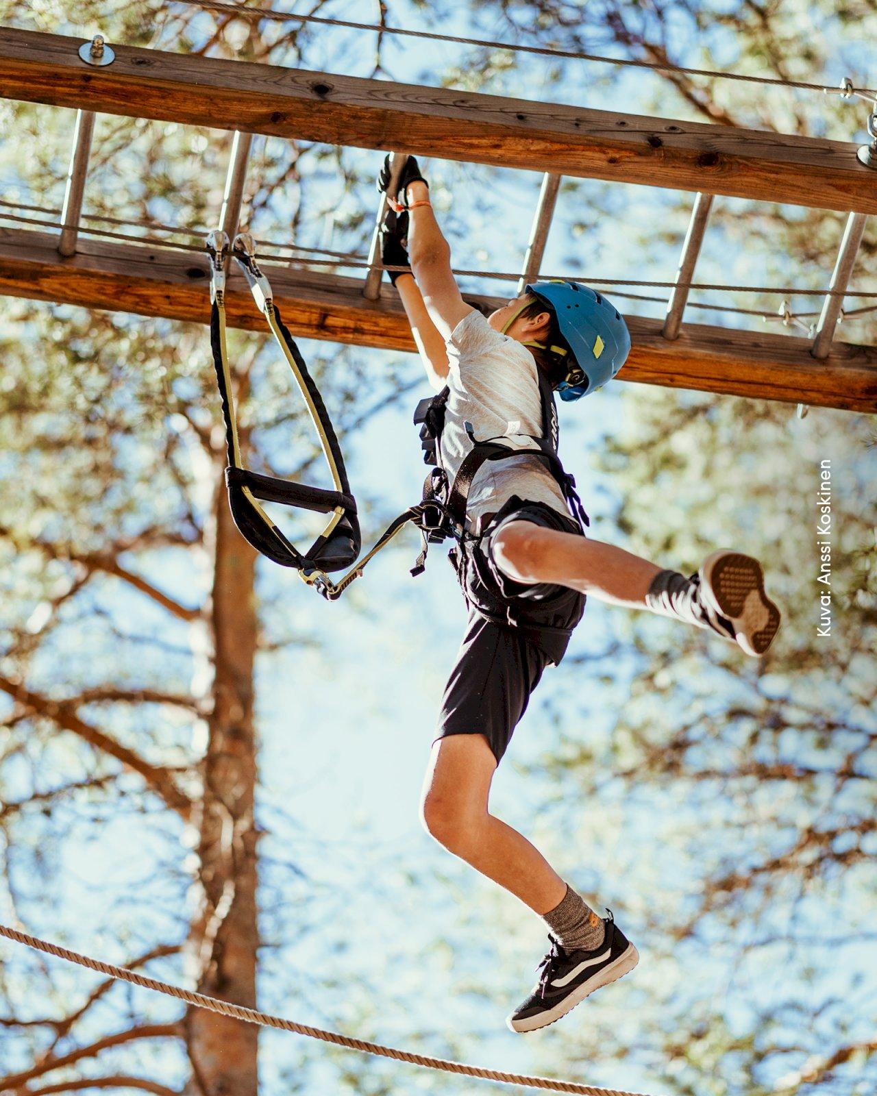 Poika roikkuu turvavaljaissa Seikkailupuisto Huikeen kiipeilyradalla.