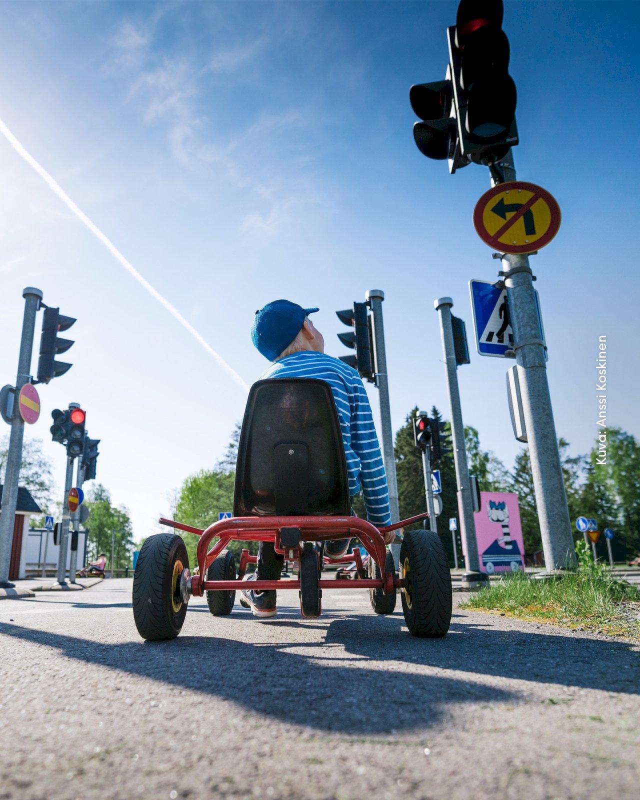 Lapsi istuu polkuautossa liikennepuisto Vinkkarissa ja odottaa punaisen valon vaihtumista.