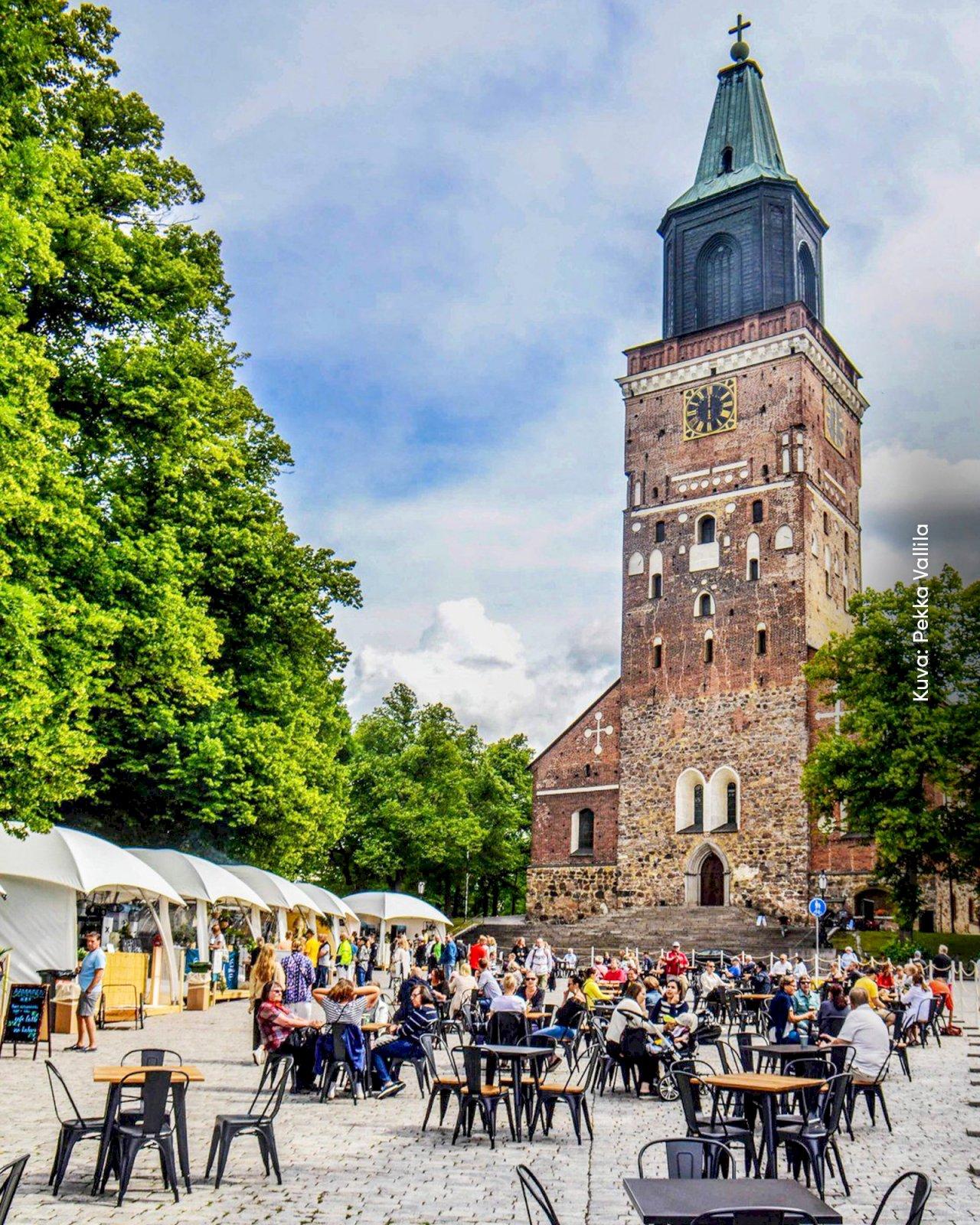 Ihmisiä syömässä ja juomassa Kirkkopuiston Terassilla Turun tuomiokirkon edessä.