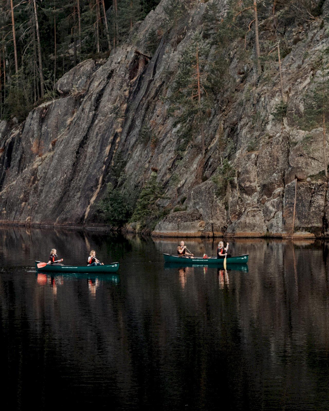 Neljä naista meloo järvellä kallioisessa metsämaisemassa.