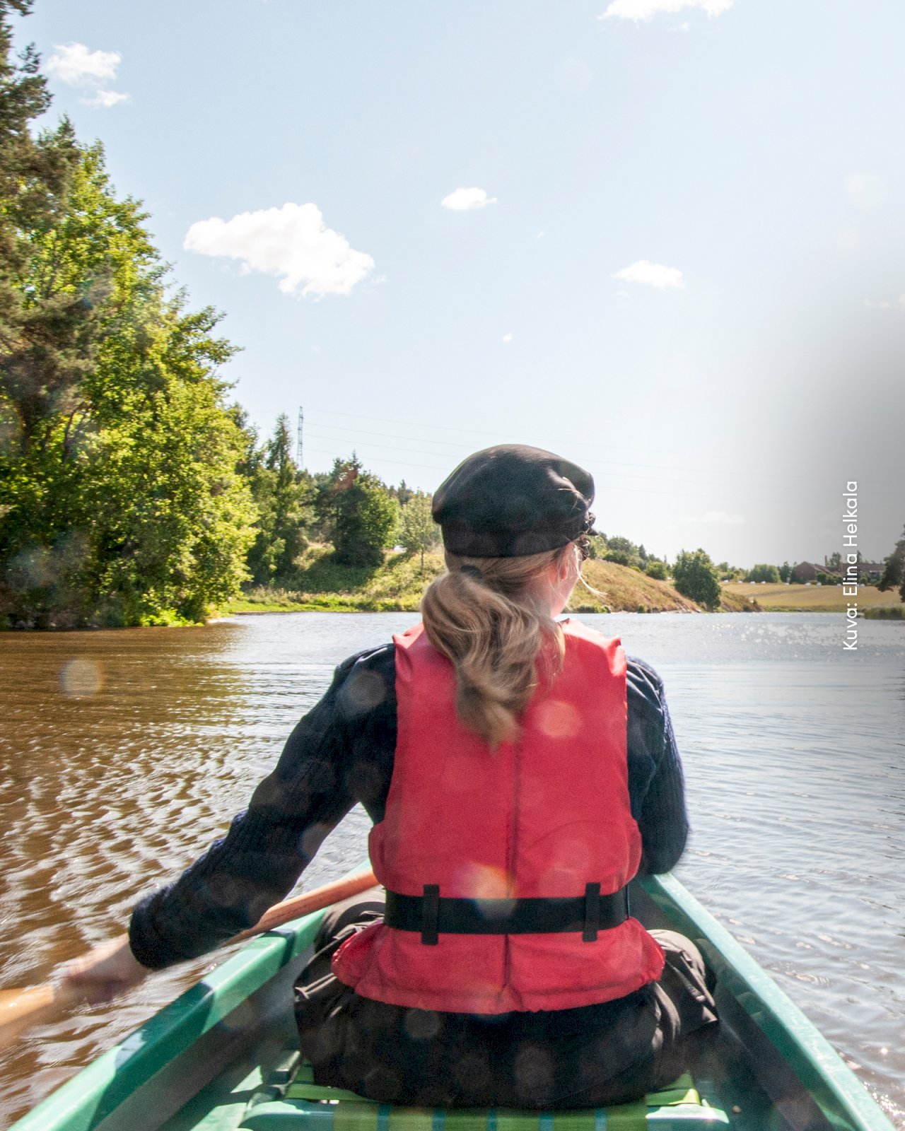 Nainen meloo kanootilla Aurajoella.