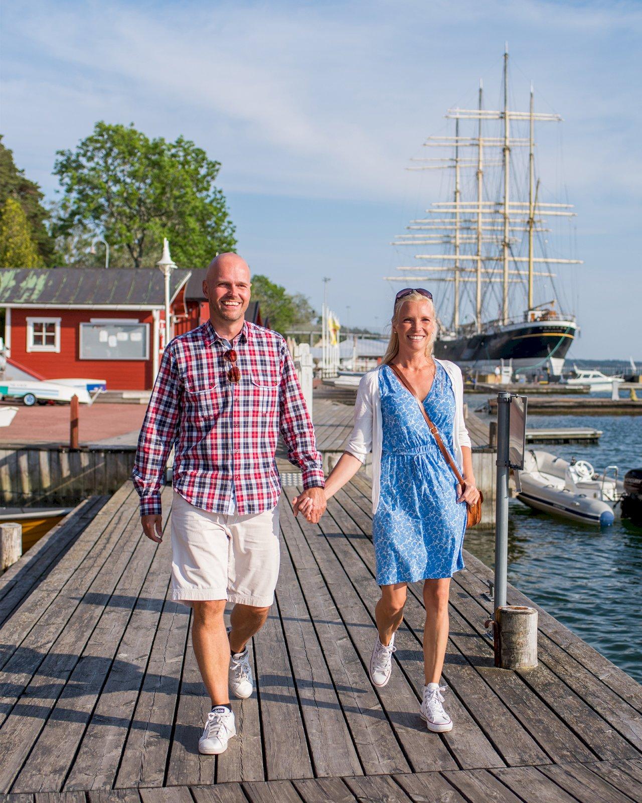 Pariskunta kävelee käsikkäin Ahvenanmaan satamassa laivojen ohi.