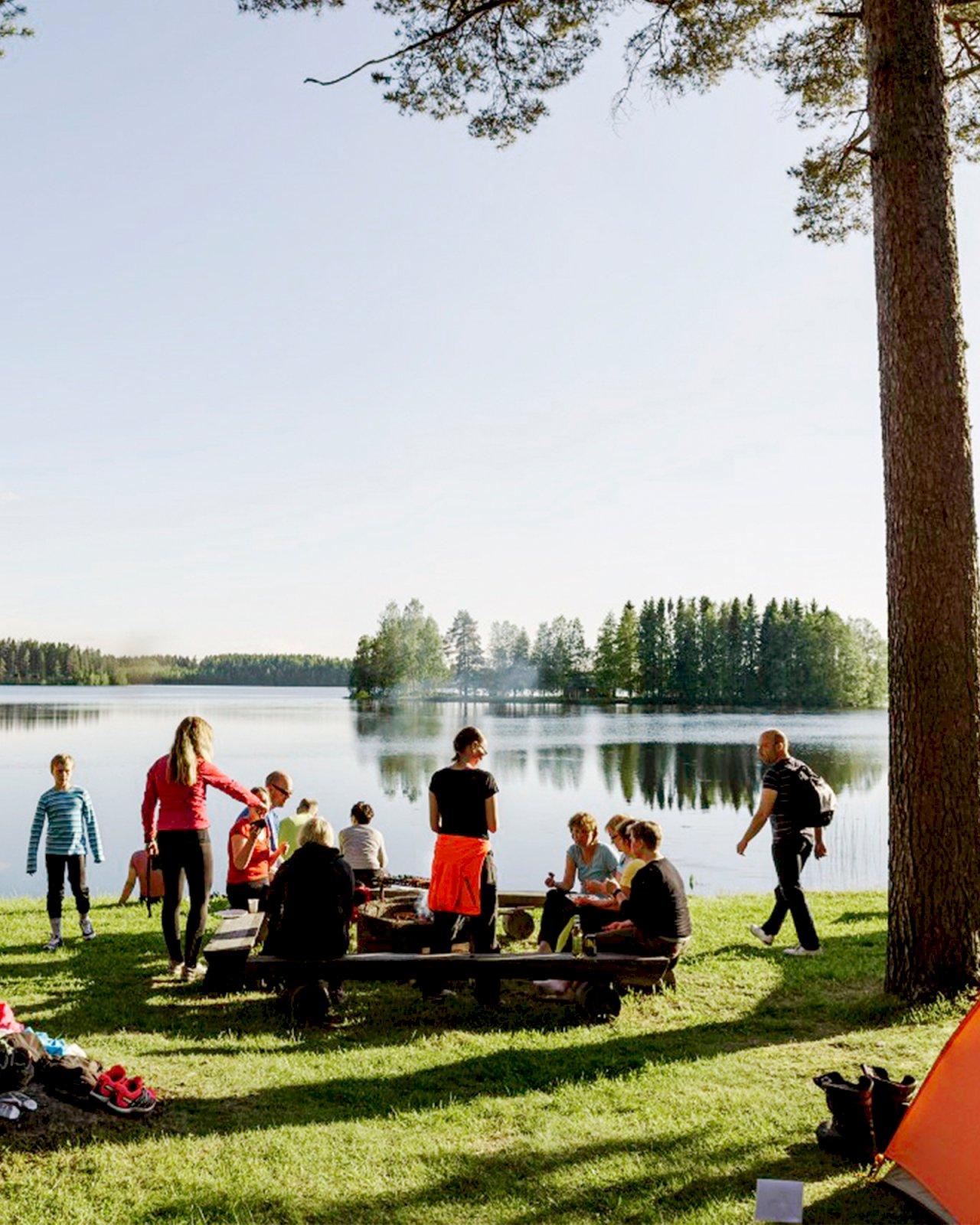 Ihmisiä telttoineen nuotiopaikalla järven rannalla Pedersöressä.