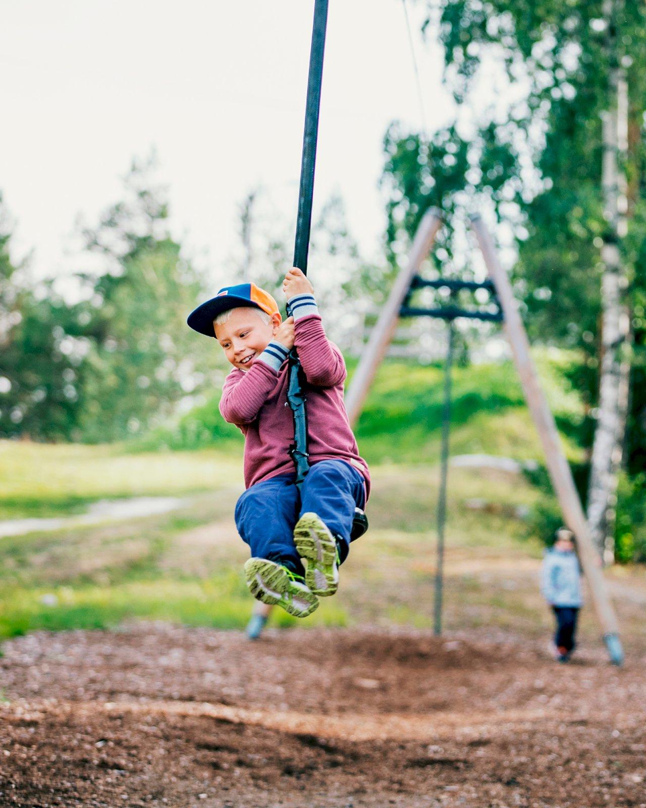 Lapsi roikkuu köyden varassa Luodon Urheilupuiston Seikkailupuistossa.