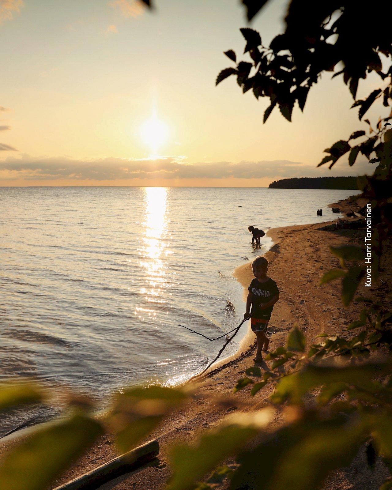 Kaksi lasta leikkii Ärjänsaaren hiekkarannalla auringonlaskussa.