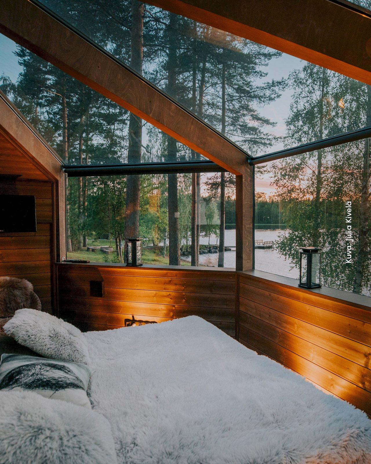 Revontuli Resortin lasikattoinen iglu-majoitus järvimaisemalla.