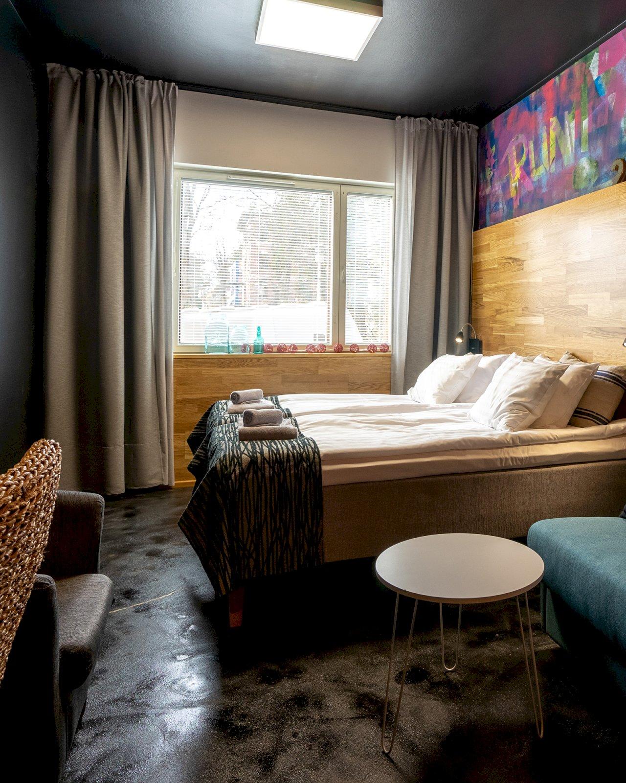 Time Hostel Jyväskylän majoitushuoneen seinää koristaa värikäs graffiti-taideteos.