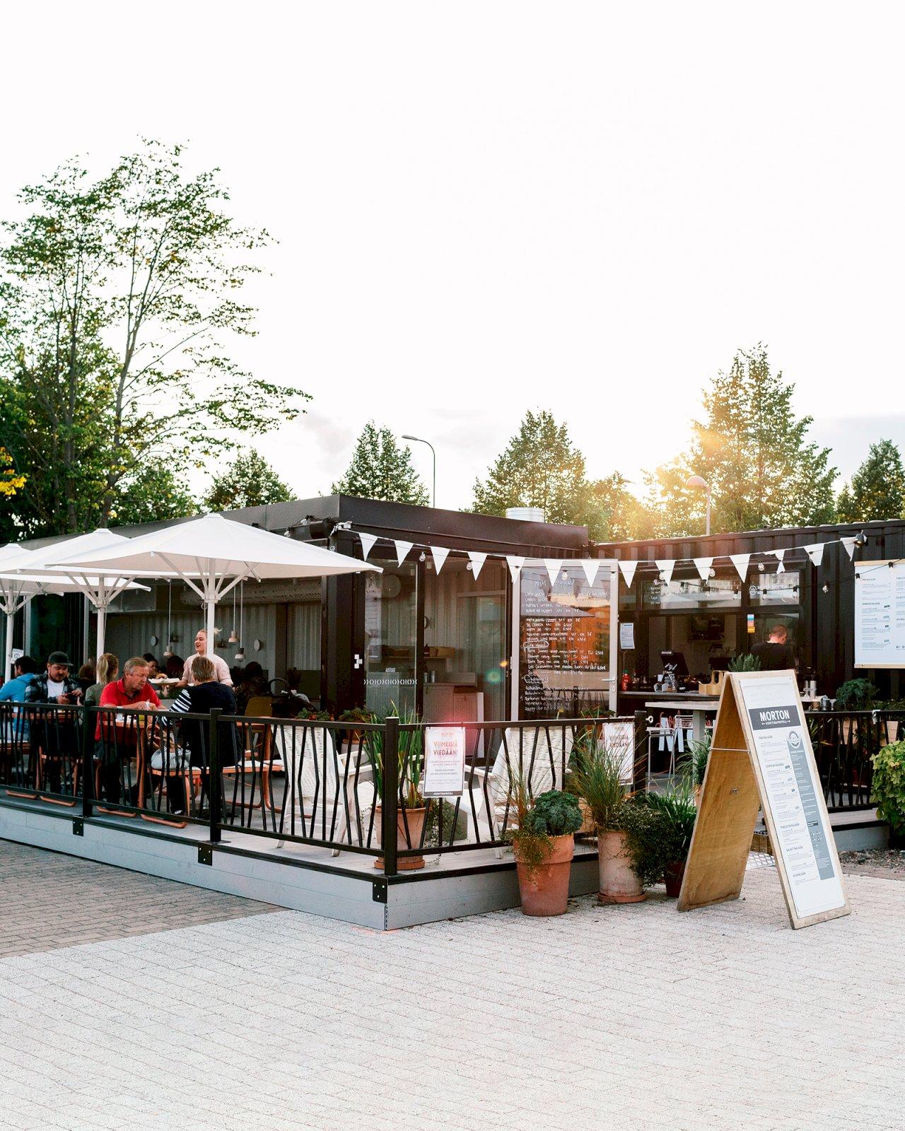 Ihmiset nauttivat kesäpäivästä Konttiravintola Mortonin rantaterassilla Jyväskylässä.