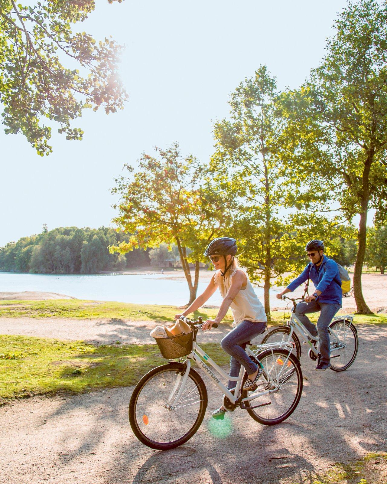 Mies ja nainen pyöräilevät Ruissalon kansanpuiston hiekkatiellä.