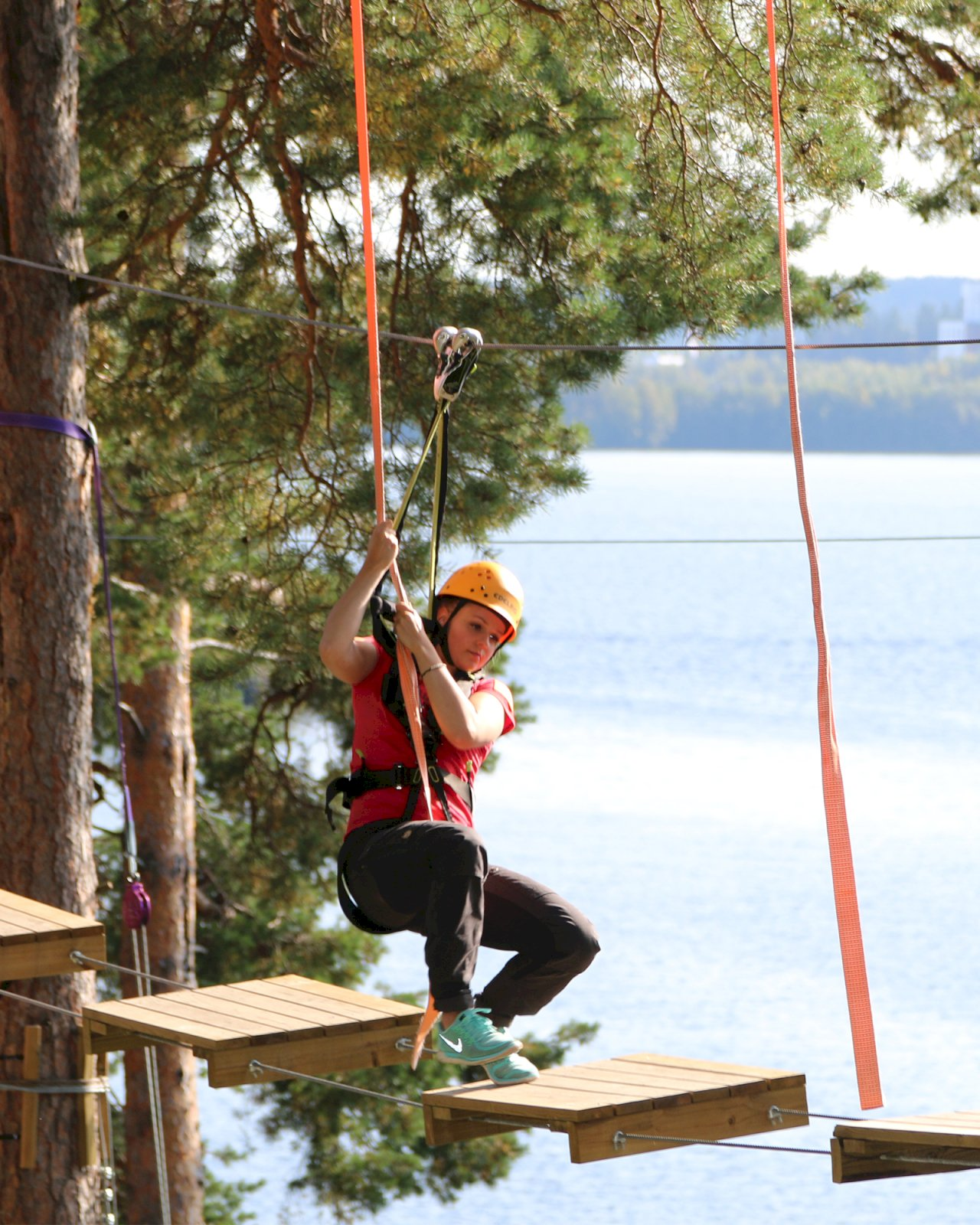 Nainen kiipeilee Varalan Flowparkin seikkailuradalla korkealla Pyhäjärven maisemissa.