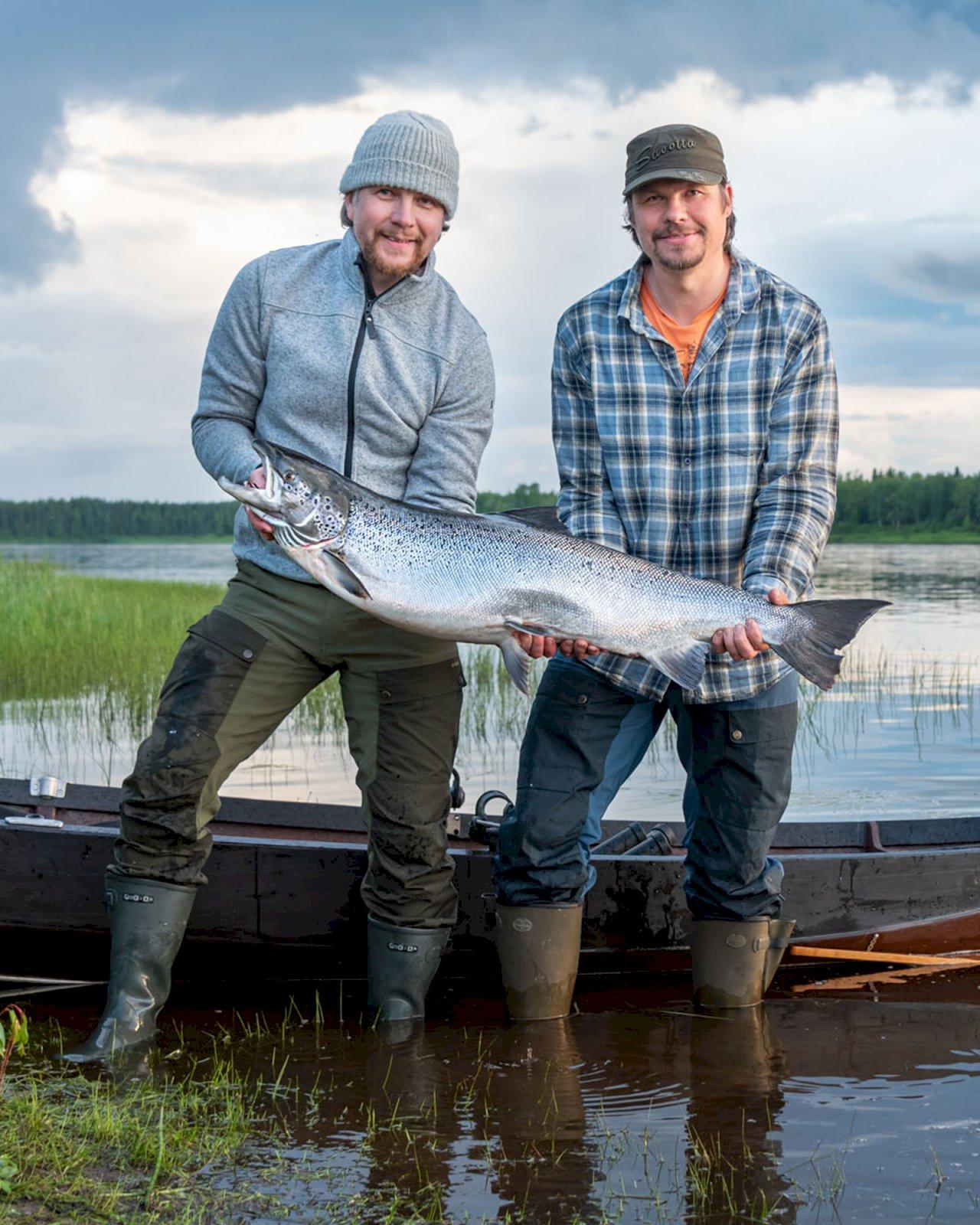 Kaksi miestä seisovat Tornionjoella ja näyttävät kameralle kalastamaansa suurta lohta.