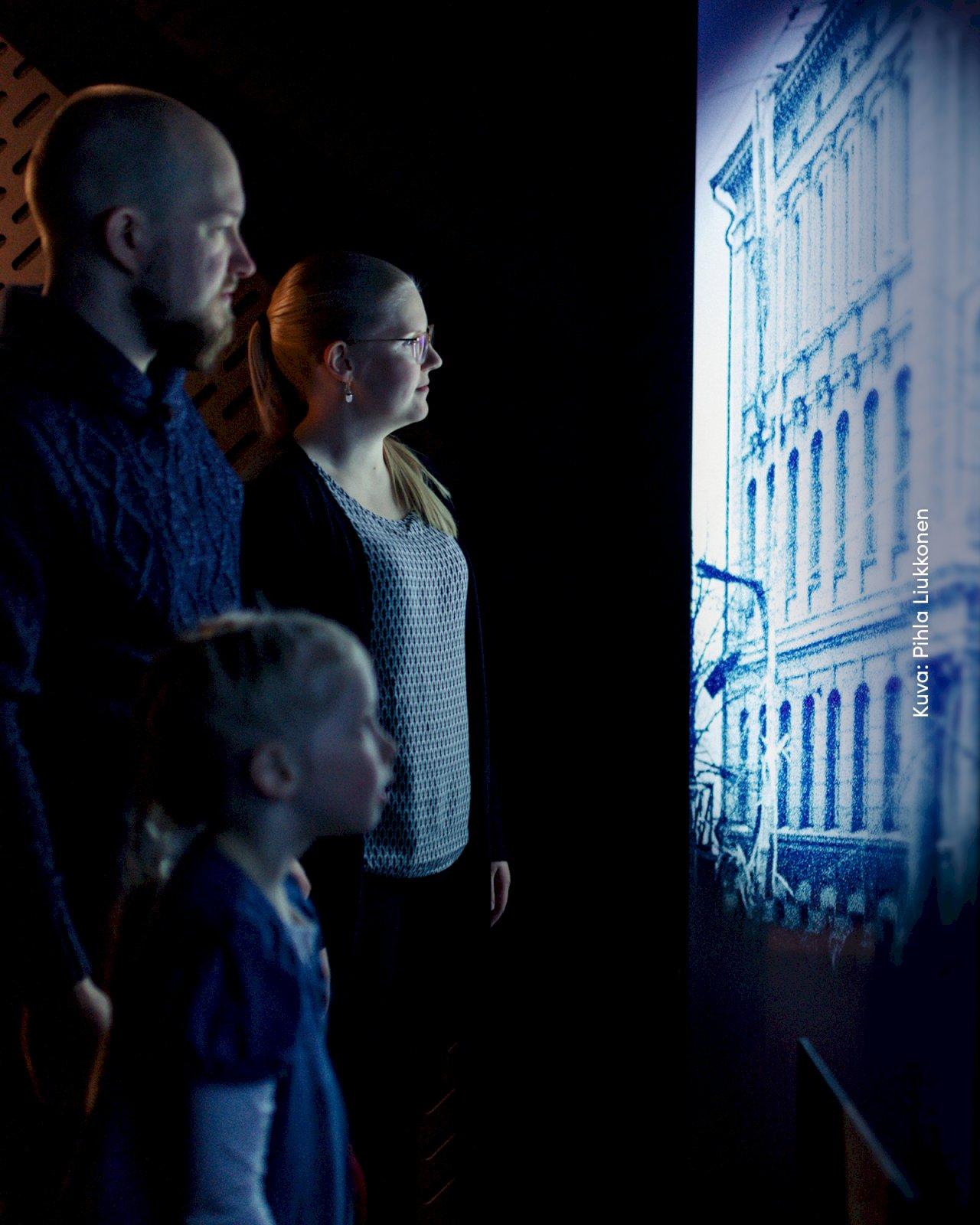 Kaksi aikuista ja lapsi tutkivat näyttelyä tiedekeskus Muistissa Mikkelissä.