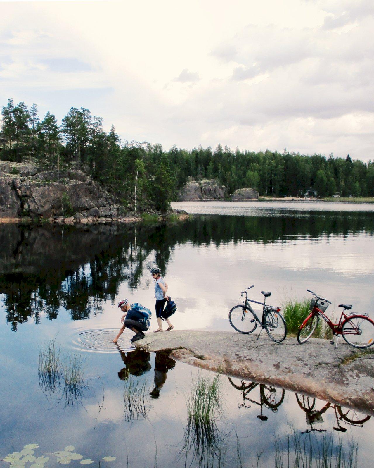 Kaksi pyöräilijää ovat pysähtyneet järven rannalle Saimaan saaristoreitin varrella.