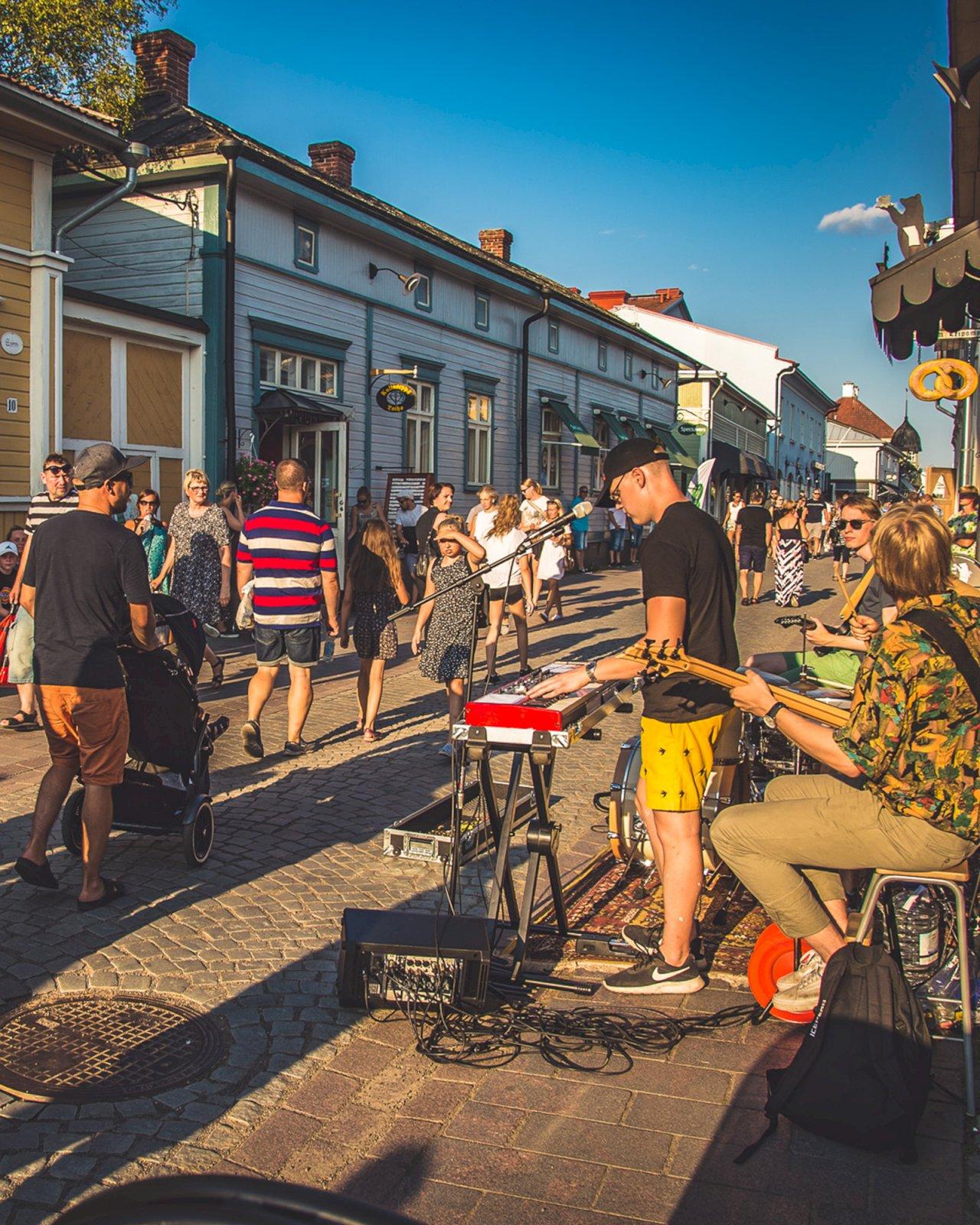 Bändi soittaa musiikkia ihmisten täyttämällä kadulla Rauman Pitsiviikoilla.