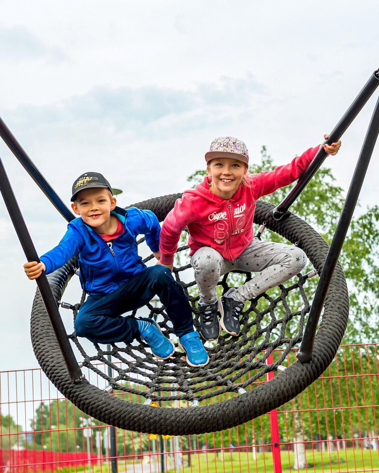 Kaksi lasta keinuvat Rauman Kipparinpuistossa.