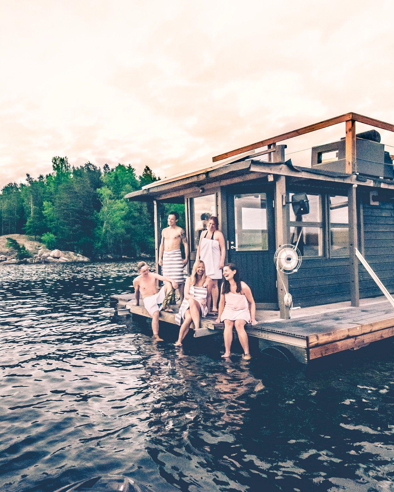 Joukko ihmisiä vilvoittelevat saunalautan kannella Lohjanjärvellä.