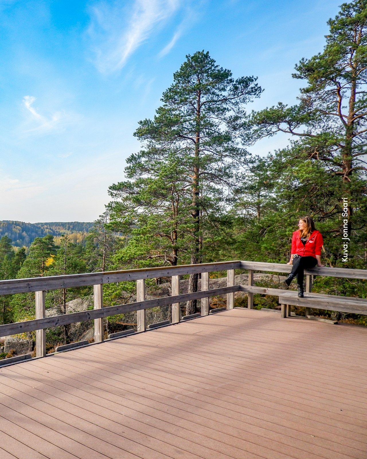 Nainen istuu luonto- ja retkeilykeskus Haltian näköalaterassilla ja ihailee metsämaisemaa.