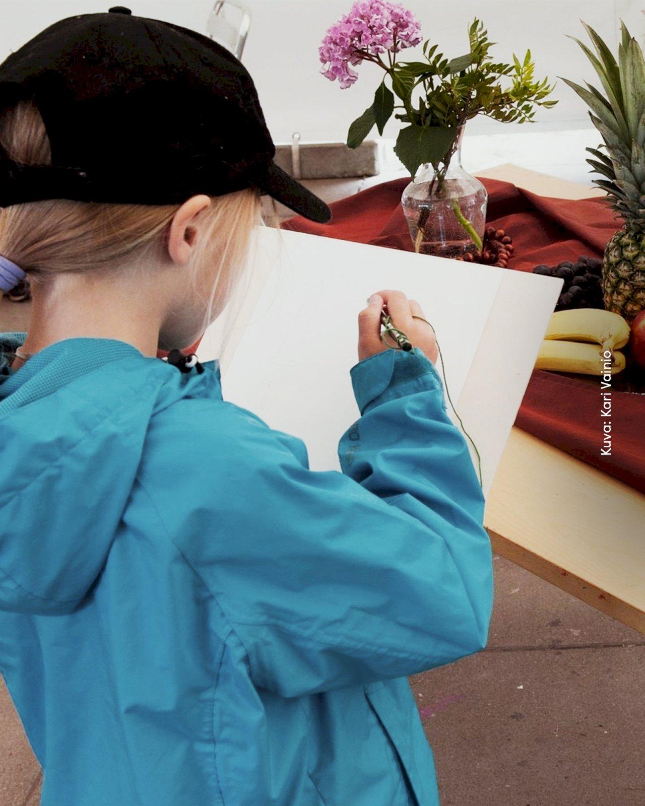 Tyttö piirtää paperille hedelmiä ja kukkia Turun Seikkailupuistossa.