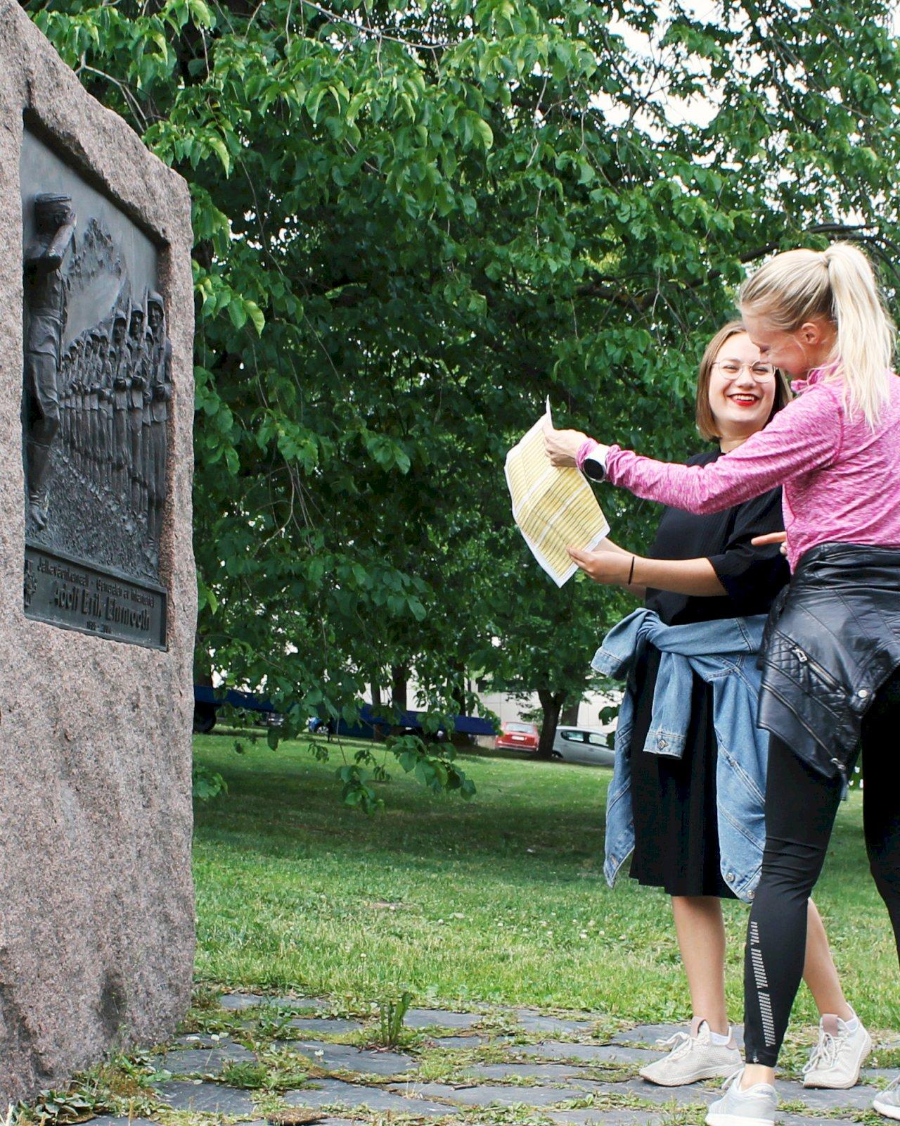 Kaksi naista seisovat muistomerkin edessä ja tutkivat Turun kulttuurikontoilun karttaa.