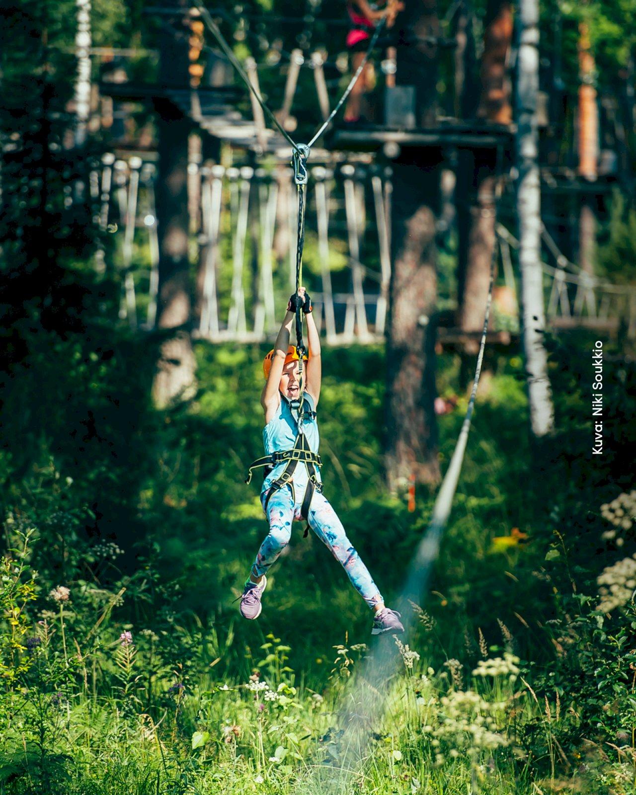 Lapsi roikkuu turvavaljaissa Pajulahden Seikkailupuistossa.